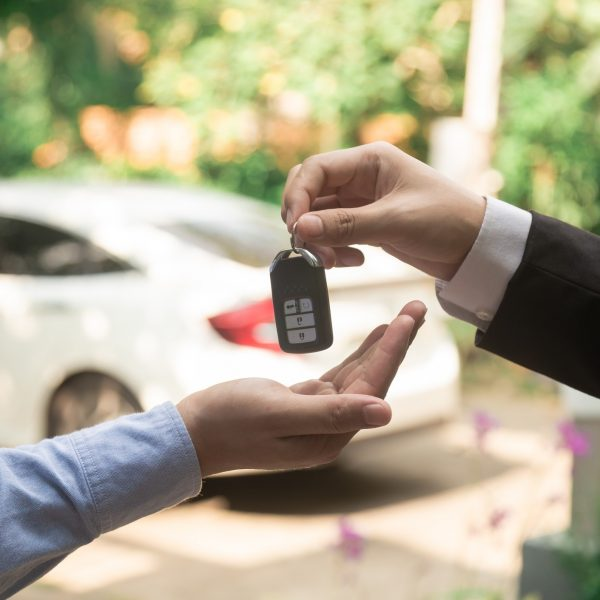 auto-business-car-sale-deal-gesture-and-people-concept-close-up-of-dealer-giving-key-to-new-owner-and_t20_pR3jbd