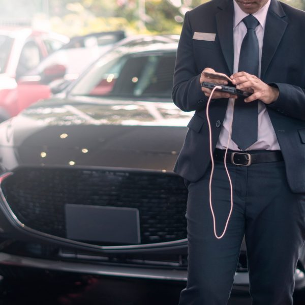 car-salesman-using-mobile-phones-and-have-new-cars-in-the-background-concept-car-salesman-stand-sell_t20_pRZAGj